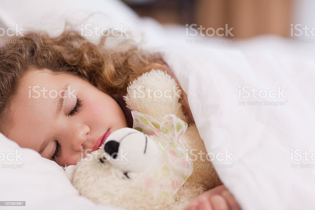 Girl sleeping with her teddy stock photo