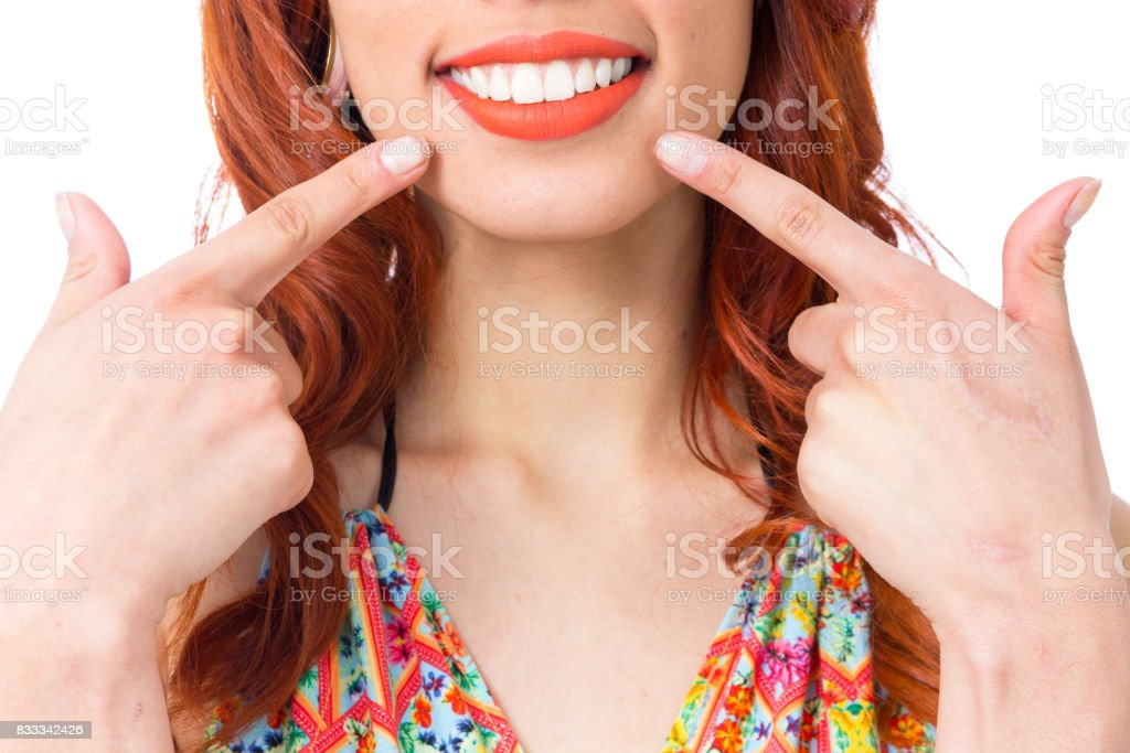 Girl smiles and points with her fingers to her lip. Extreme close up. Redhead woman is wearing a colorful summer dress. Fashion and style. Vacation and summer. stock photo