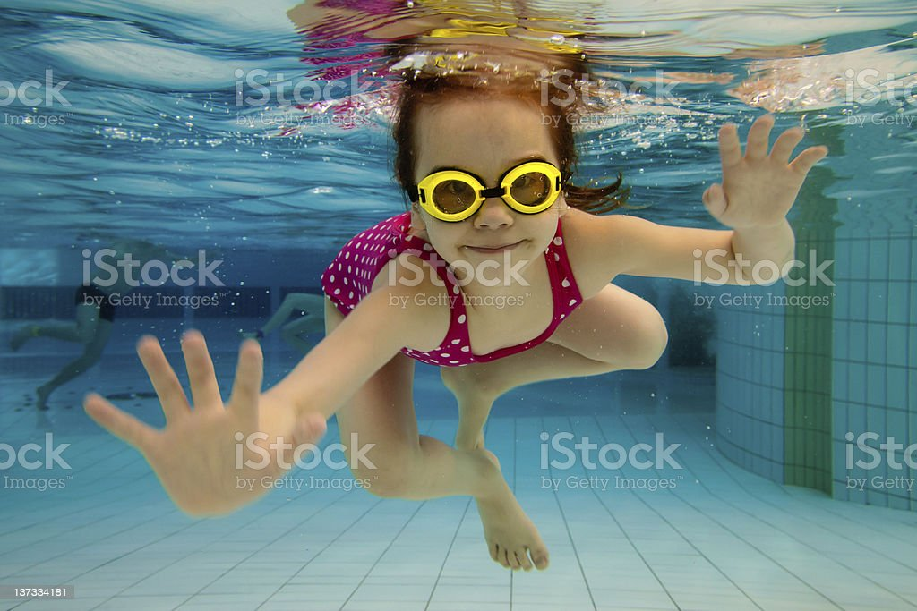Girl smiles, swimming under water in the pool stock photo