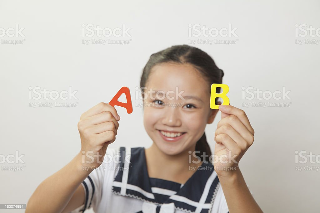 Girl smiling and holding plastic letters, Studio royalty-free stock photo