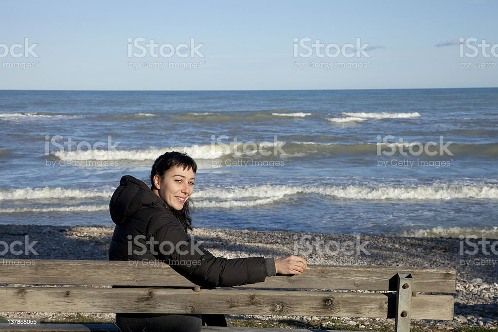 Girl smiling on a bench in front of the sea stock photo