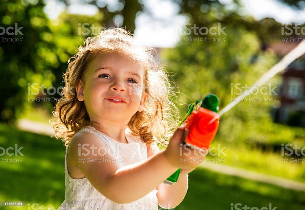 Girl smiling while splashing water with squirt gun royalty-free stock photo