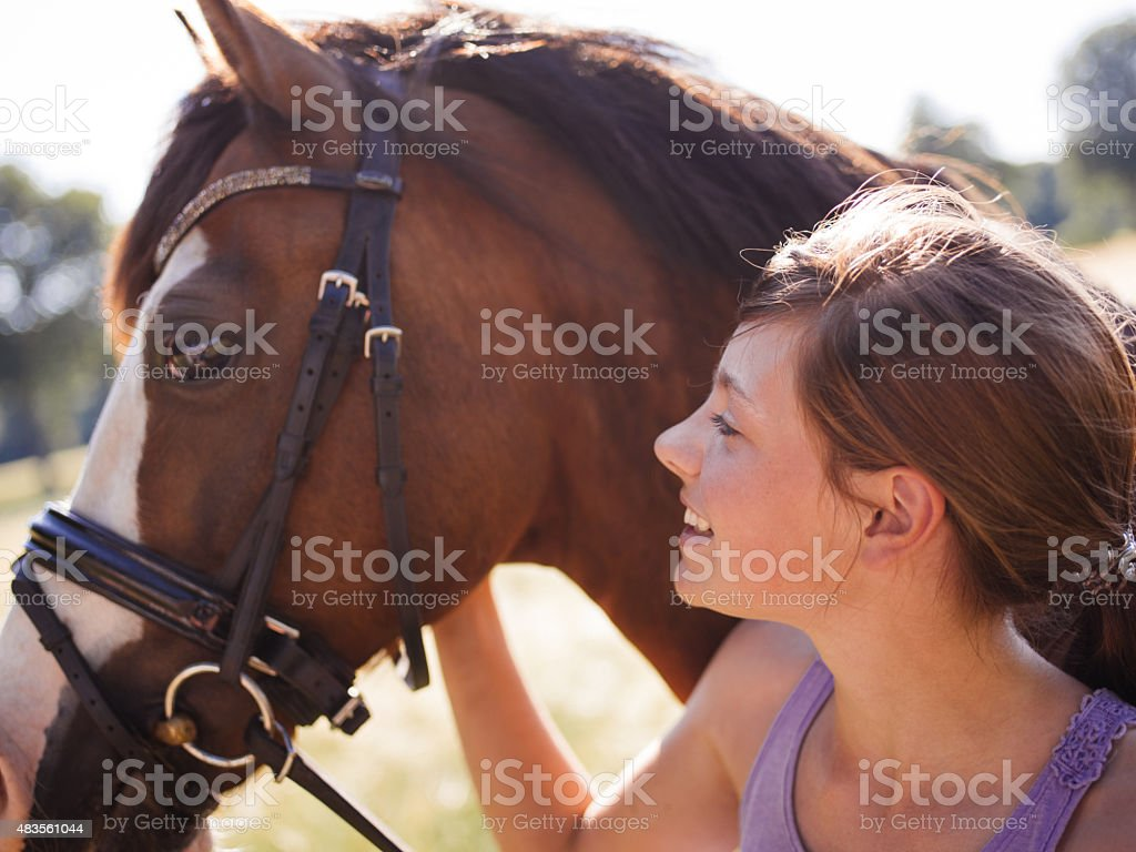 Girl smiling while walking with her horse stock photo