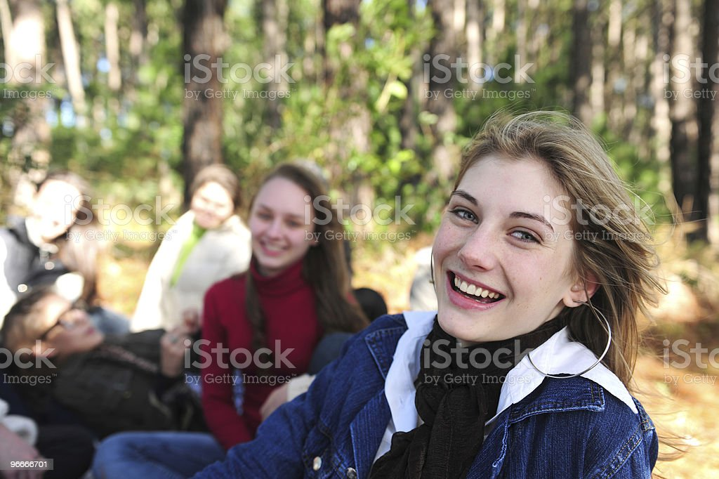 girl smiling with a group of friends in the forest stock photo