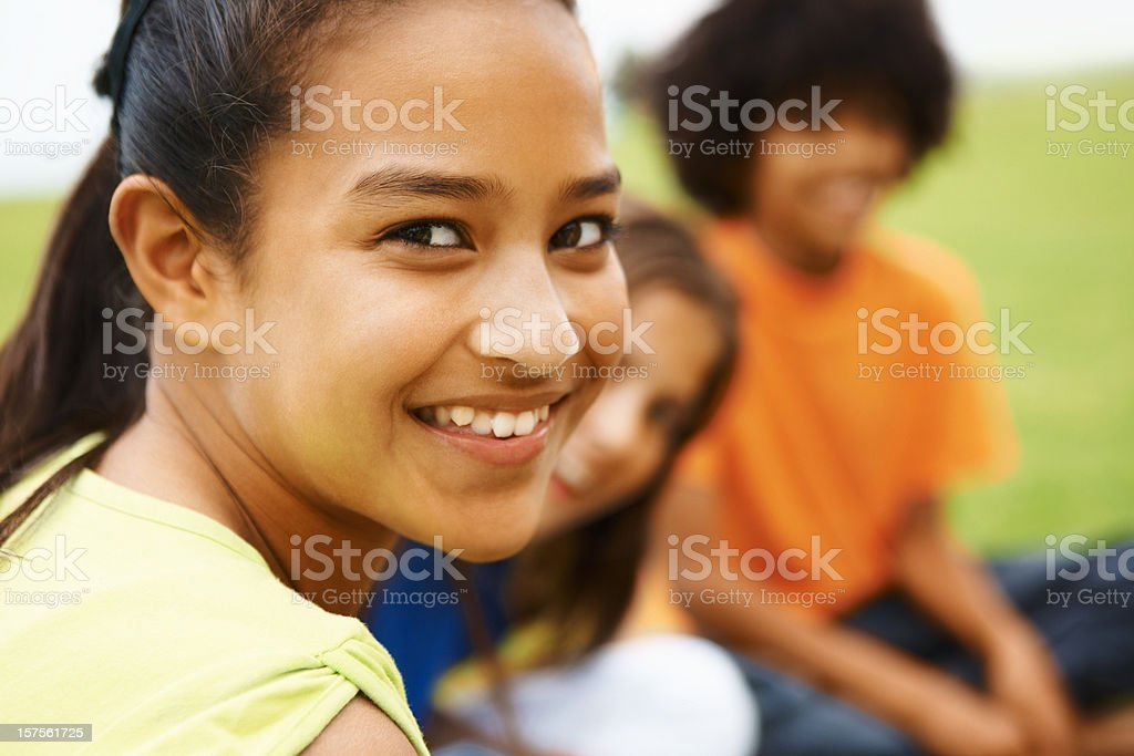 Girl smiling with her friends in the background royalty-free stock photo
