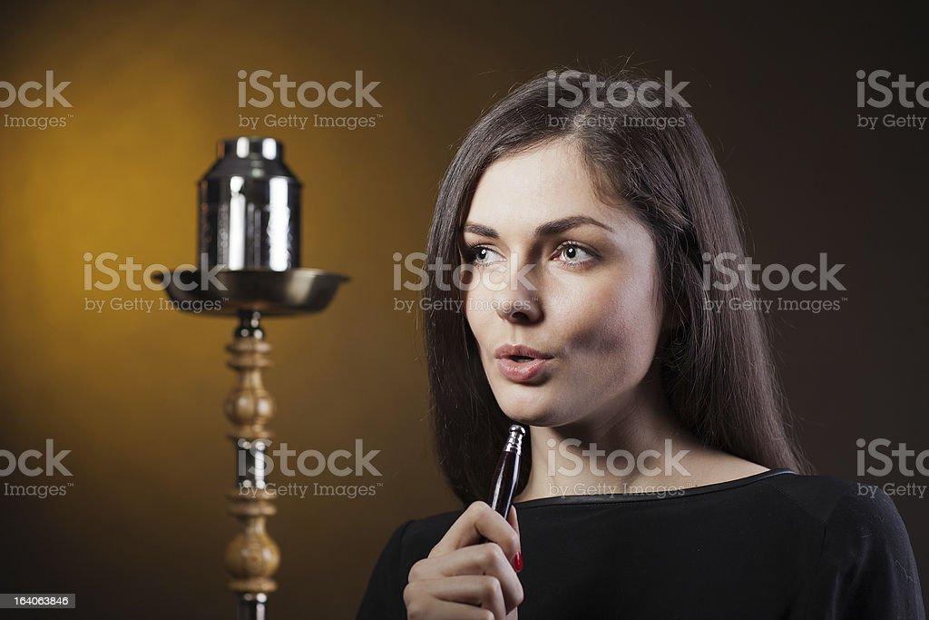 girl smokes a hookah in studio royalty-free stock photo