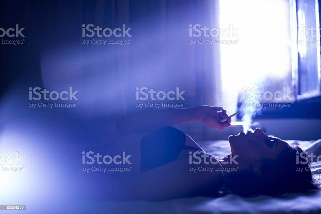 Girl smoking in bedroom stock photo