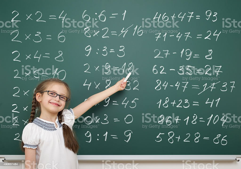 girl solve math on school board stock photo