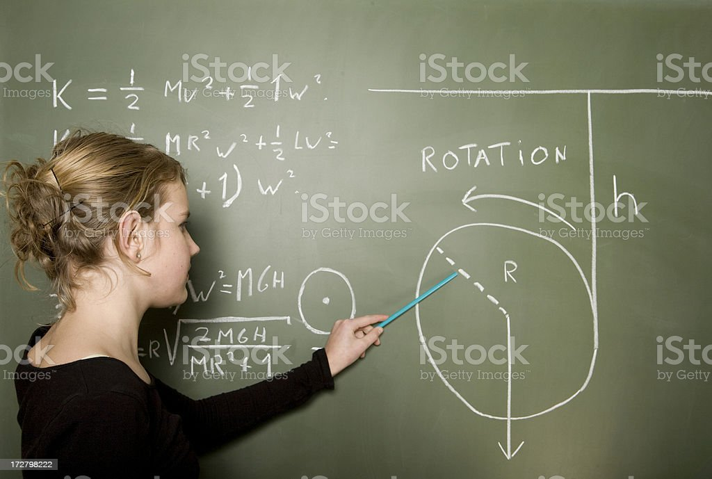 Girl solves a mathematical problem on the blackboard royalty-free stock photo