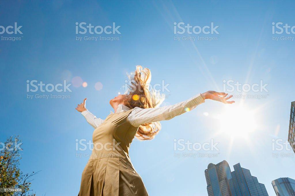 Girl spinning outside in sunshine stock photo