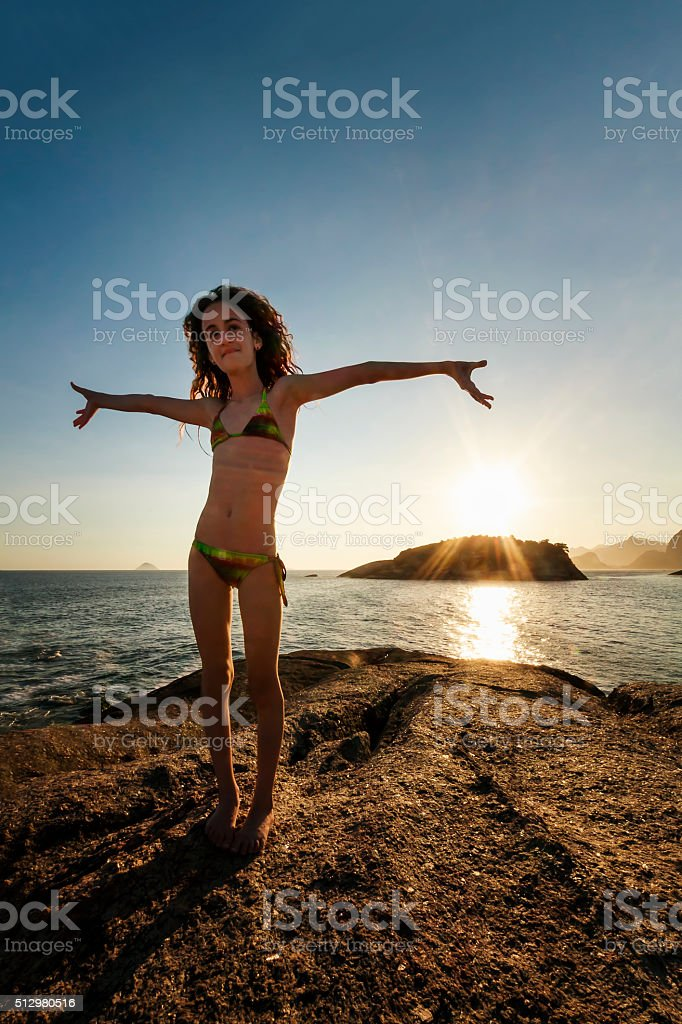 Girl Spreading Her Arms on Top of Cliff at Sunset stock photo