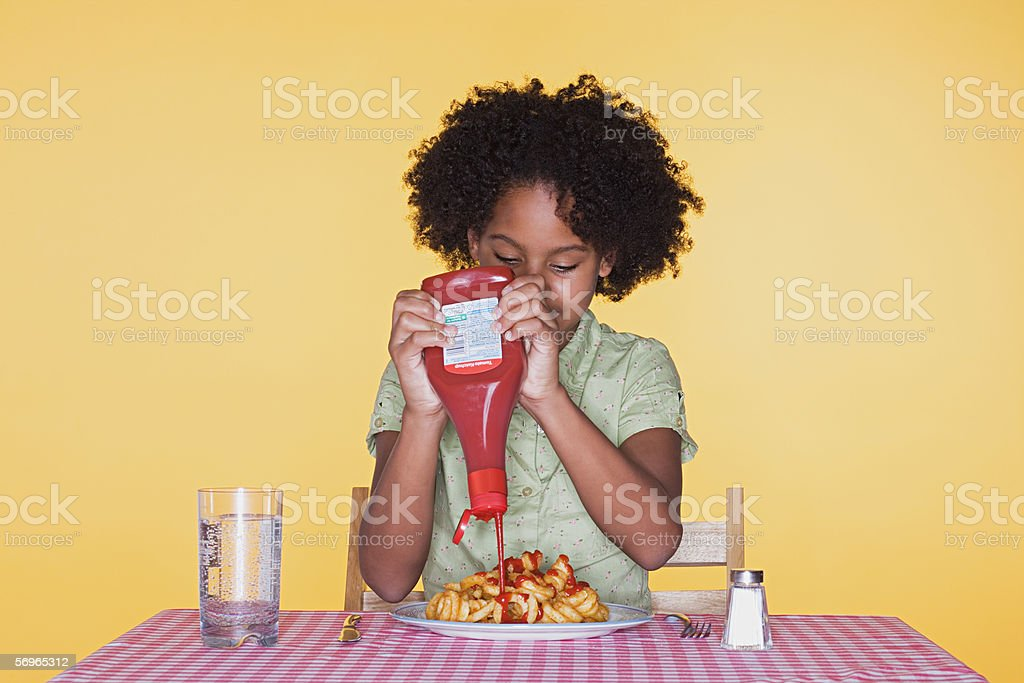 Girl squeezing ketchup onto curly fries stock photo