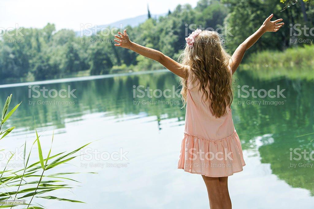 Fille debout au lakeside à bras ouverts. photo libre de droits