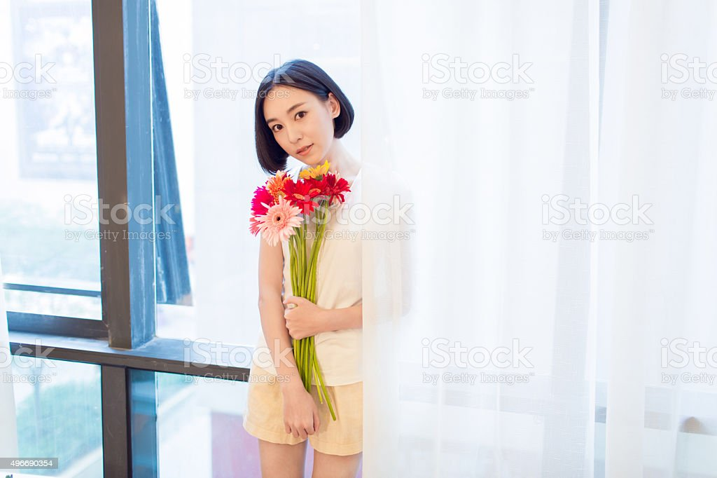 girl standing by the window stock photo