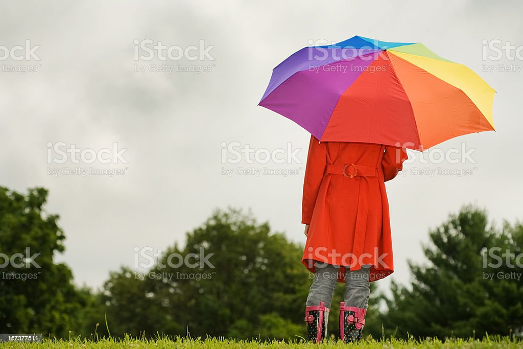 Girl standing in field under a multicolored umbrella royalty-free stock photo