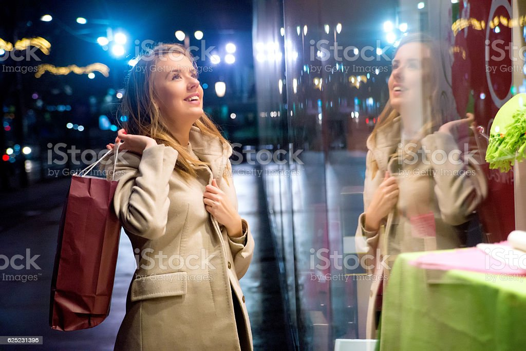 girl standing in front of a boutique holding shopping paperbag stock photo