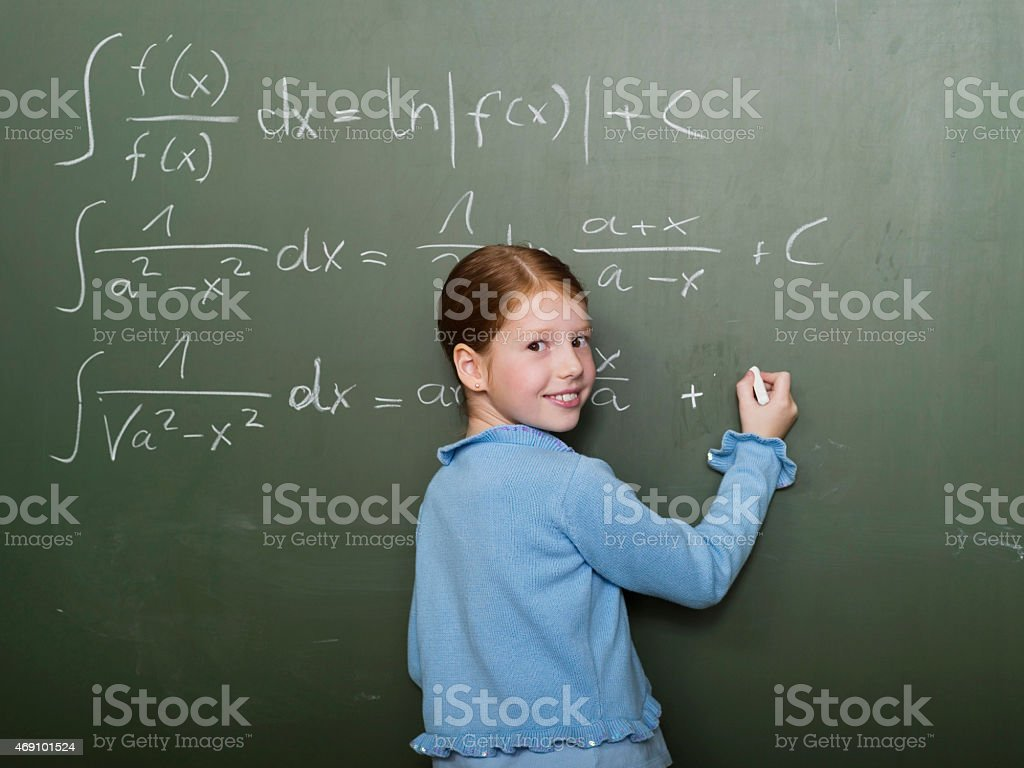 Girl standing in front of blackboard, solving arithmetic problem stock photo