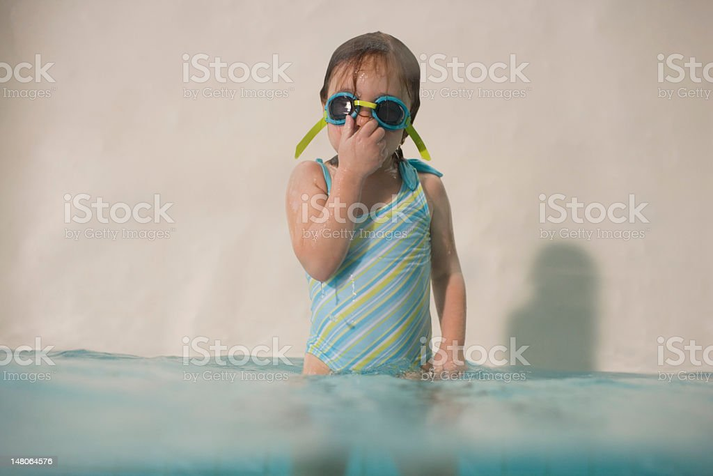 Girl (3-5) standing in swimming pool, wearing goggles and holdin royalty-free stock photo