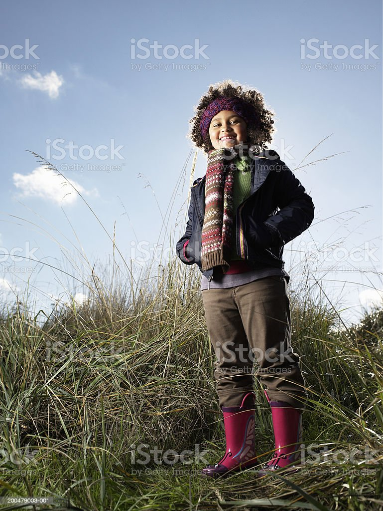 Girl (5-7) standing in tall grass, hands in pockets, smiling, portrait royalty-free stock photo