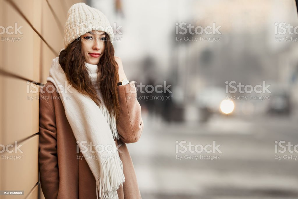 Girl standing near the wall and looking at camera. Blur yellow background stock photo