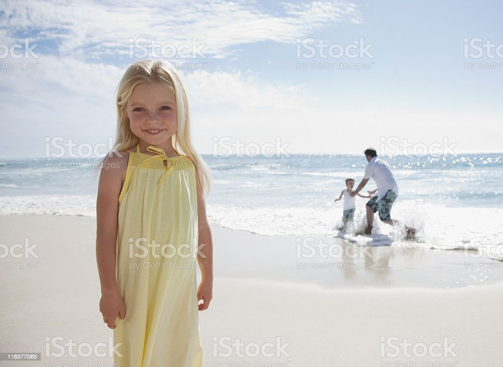 Girl standing on beach with father and brother playing in ocean royalty-free stock photo