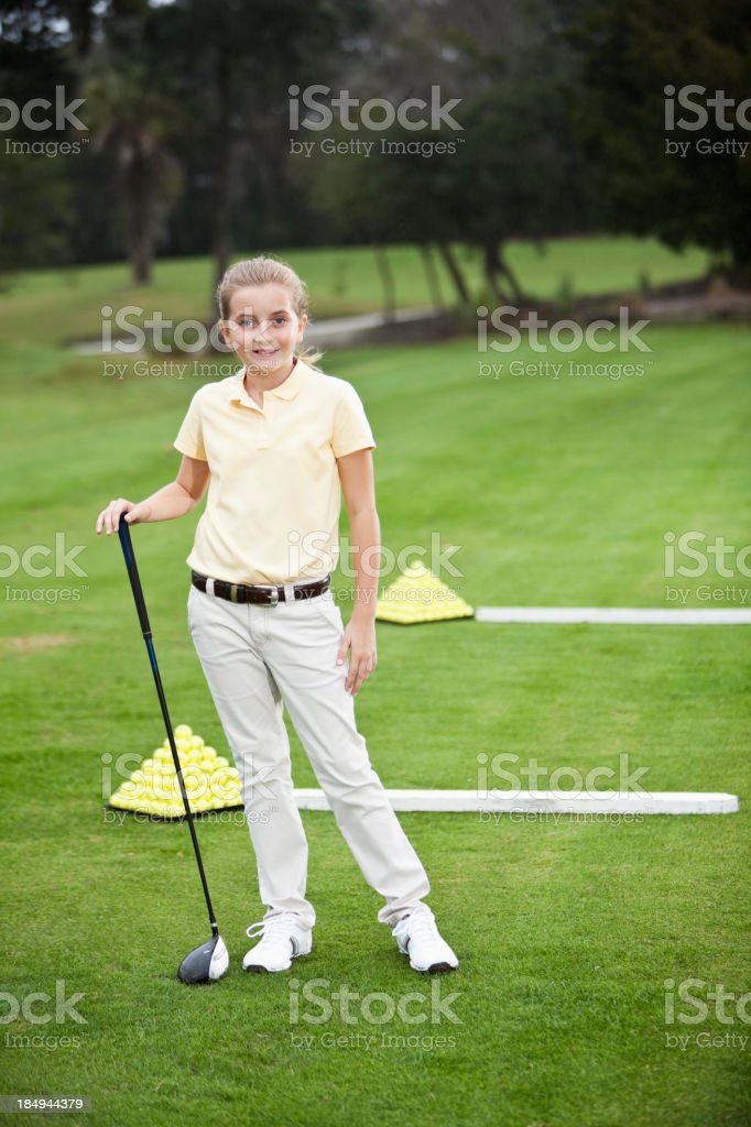 Girl standing on golf driving range stock photo