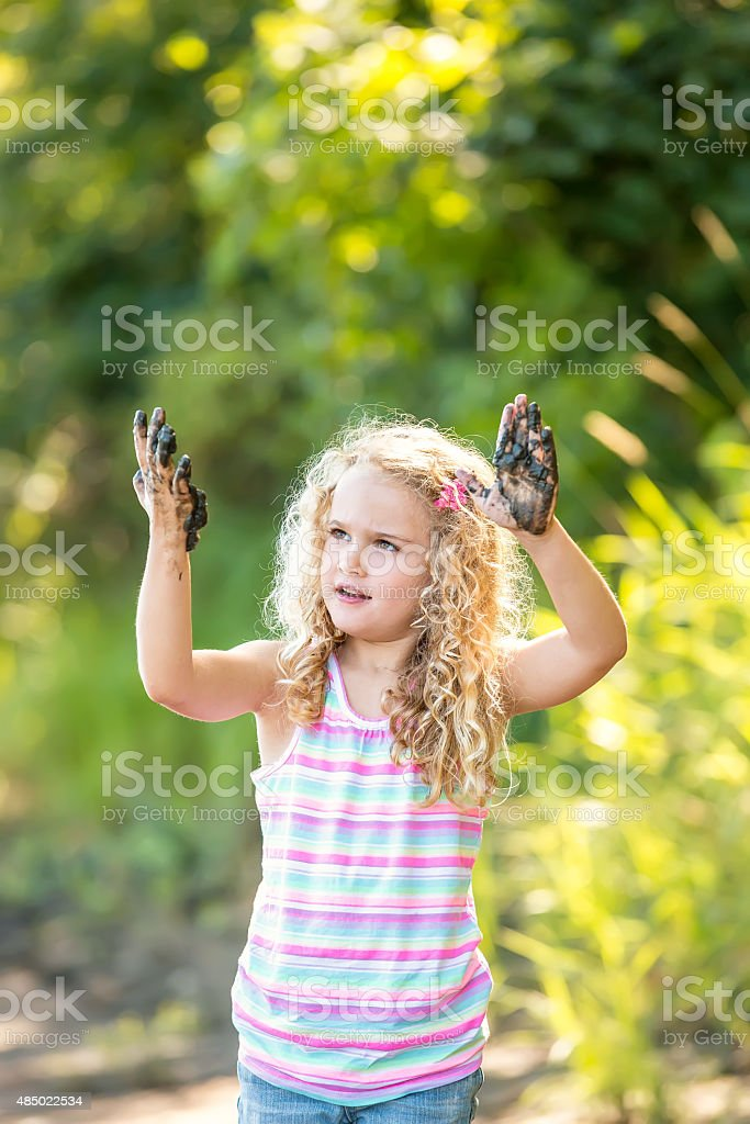 Girl Standing on Riverbank With Muddy Hands stock photo