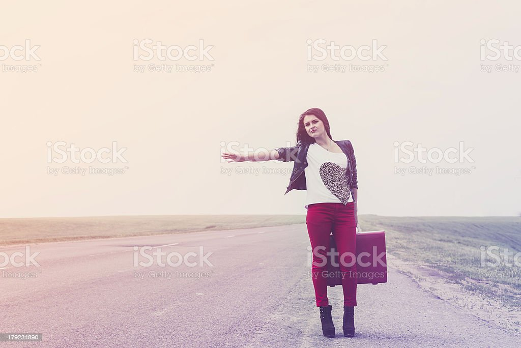girl standing on road with suitcase looks for fellow traveler royalty-free stock photo