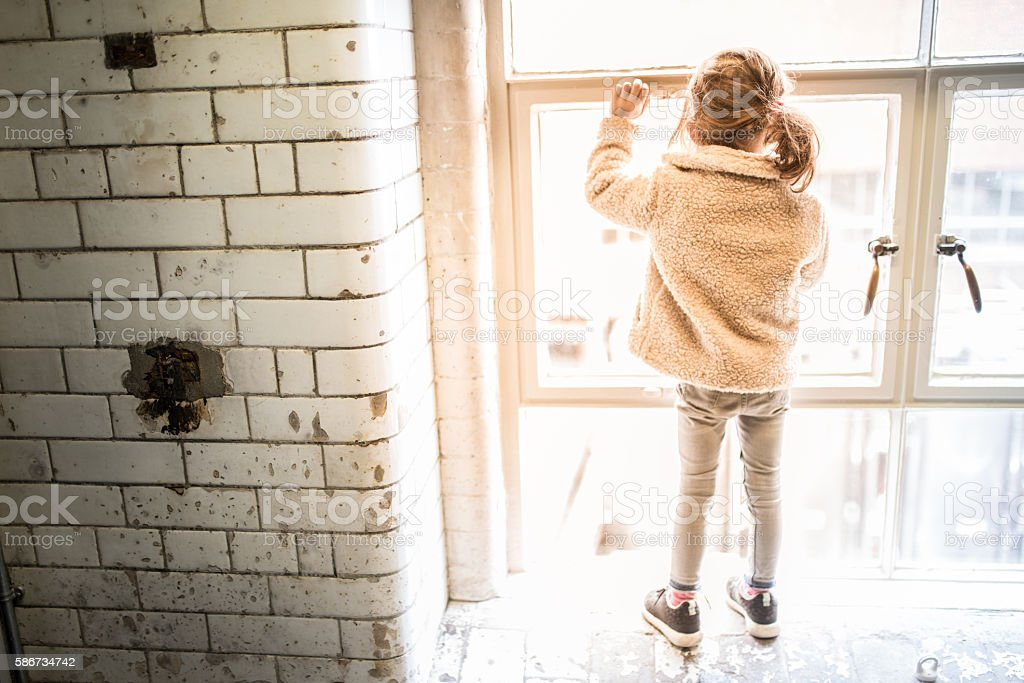 Girl standing on the window sill watching outside stock photo