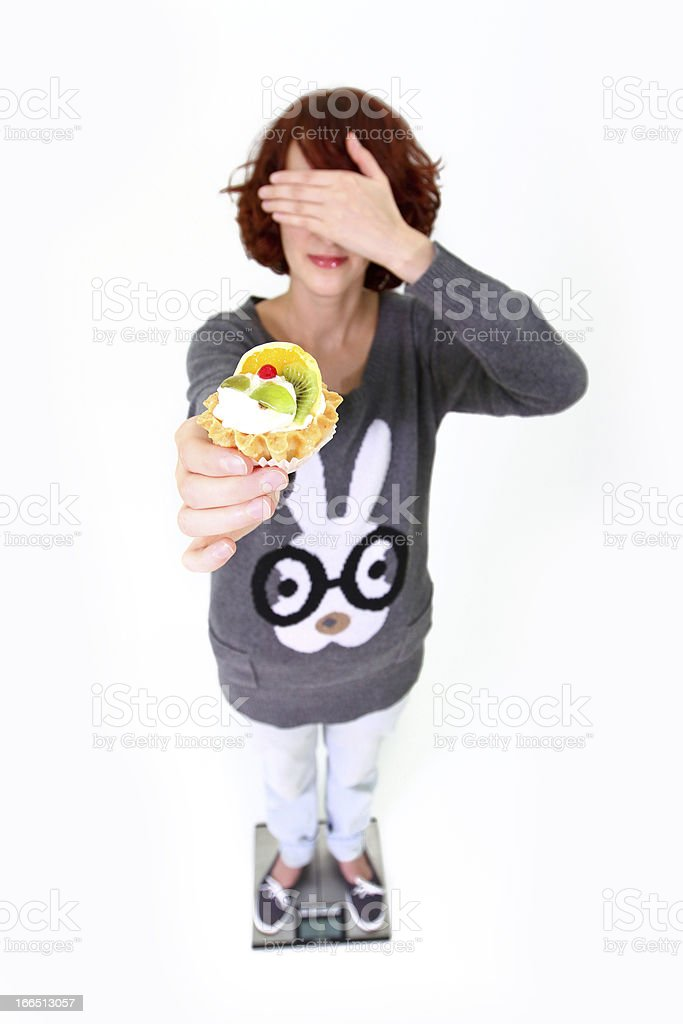 Girl standing on weigher, holding  cake and shutting her eyes royalty-free stock photo