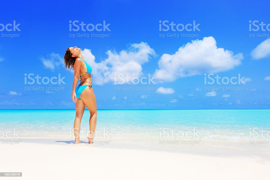 Girl standing on white sand beach against azure sea. royalty-free stock photo
