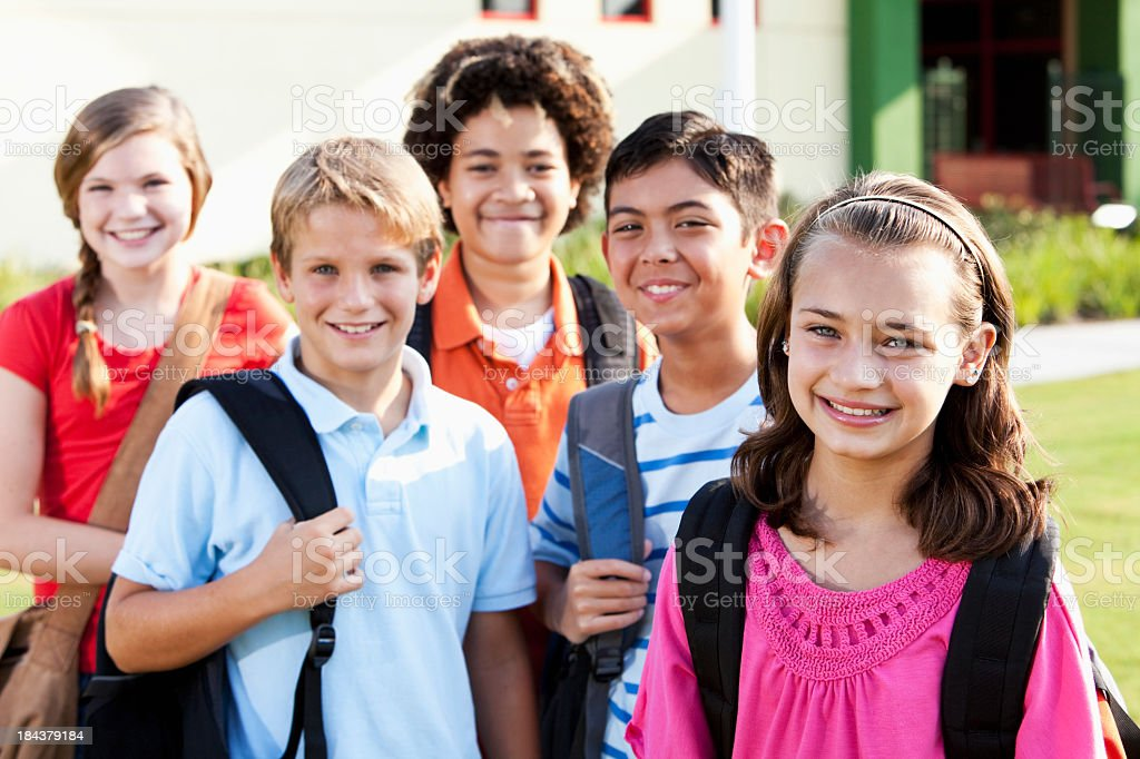 Girl standing outside school with group of friends stock photo