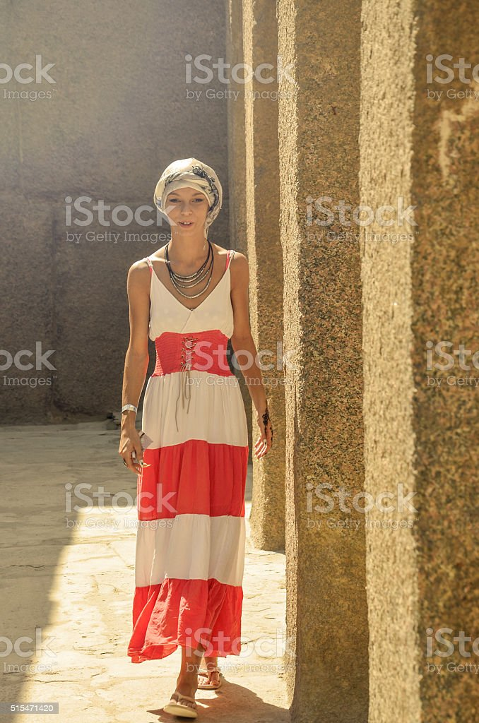 Girl stands near the Egyptian pillar of Giza stock photo