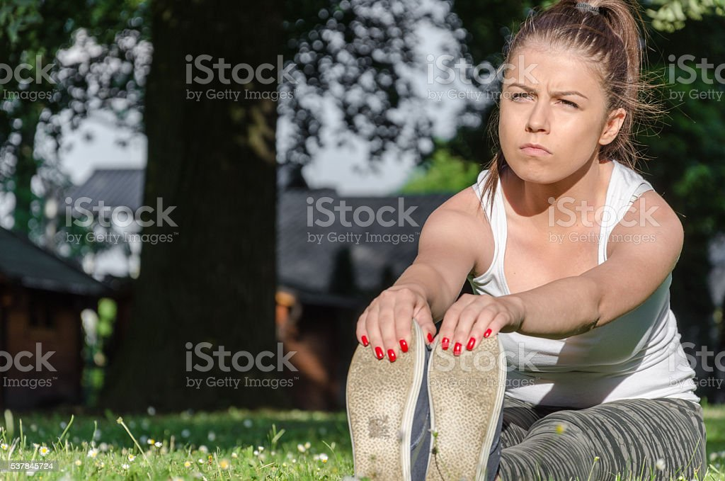 girl stretches the muscles and ligaments in nature stock photo