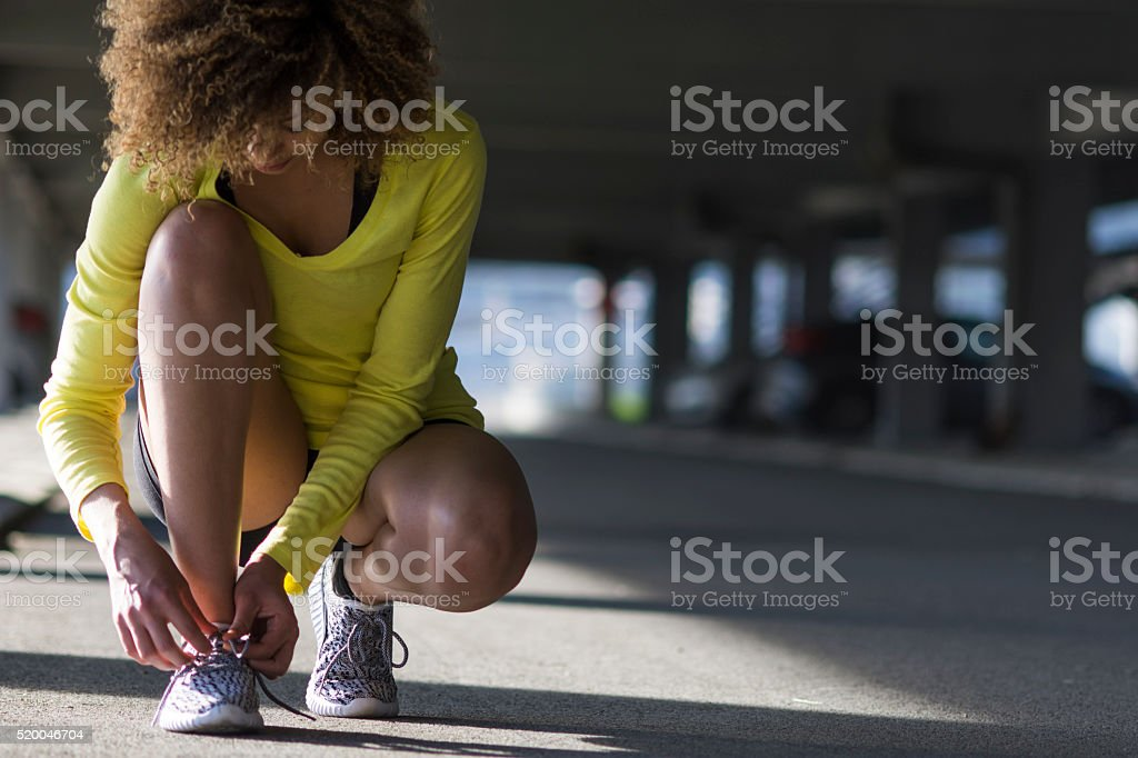 Girl stretching and listening to the music on her headphones stock photo
