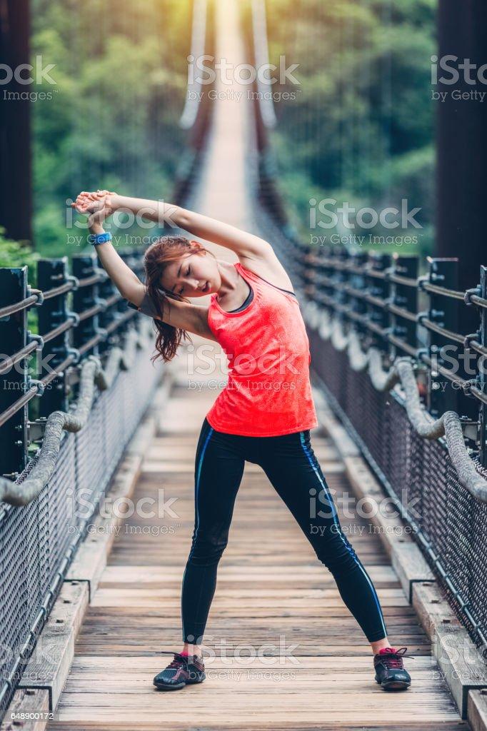 Girl stretching at the bridge stock photo