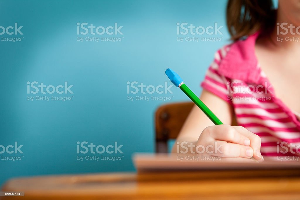 Girl Student Doing Work at School Desk, with Copy Space royalty-free stock photo