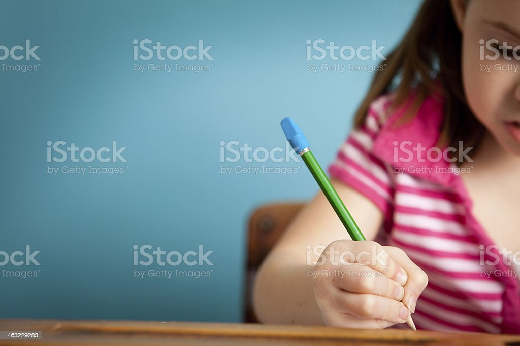 Girl Student Doing Work at School Desk, with Copy Space stock photo