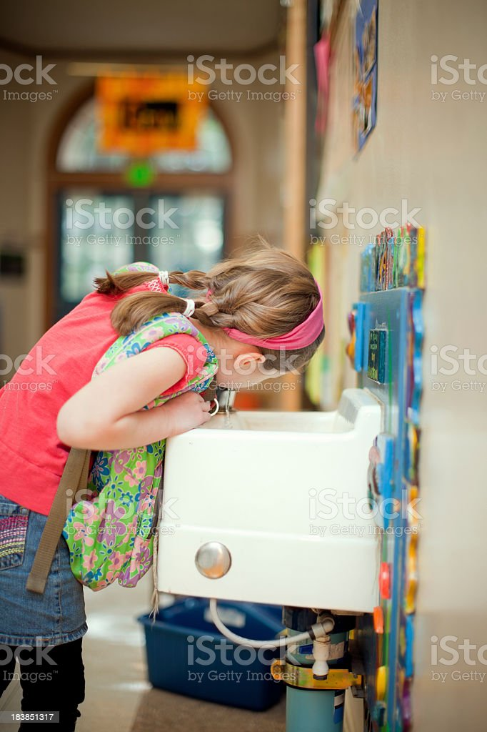 Girl Student Drinking from Fountain at School stock photo