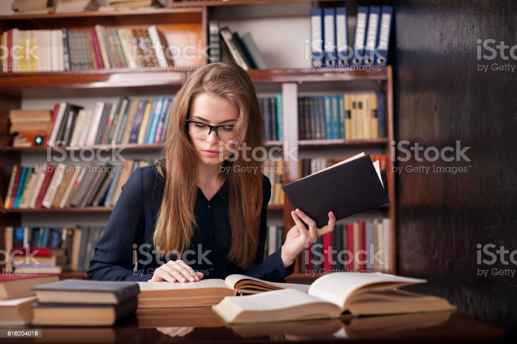 girl student sits in the library reading stock photo