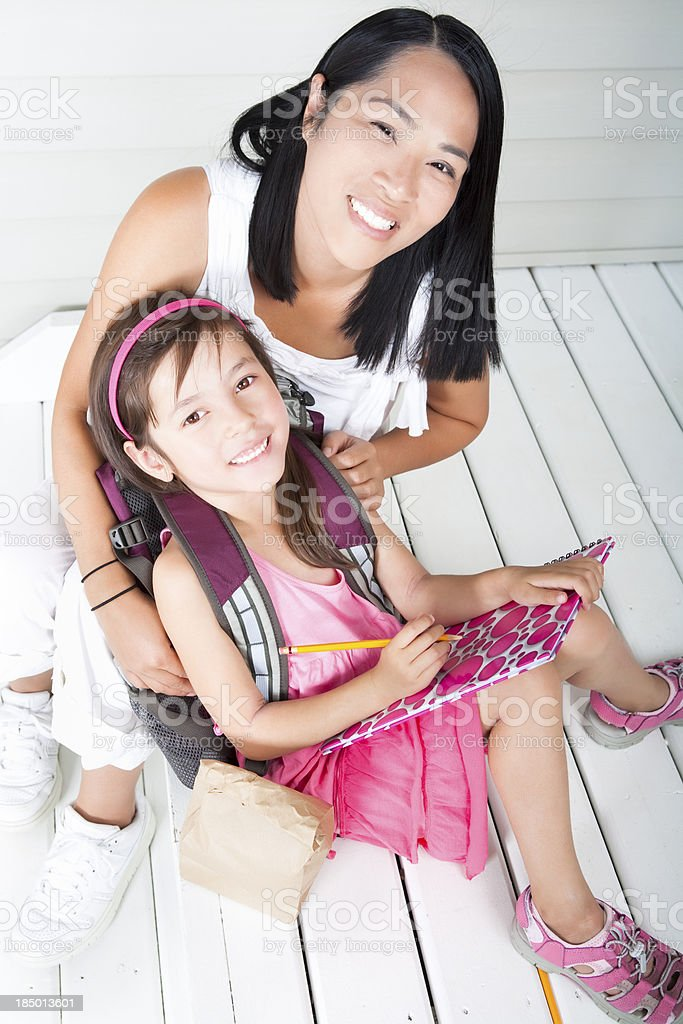Girl student sitting with mother at front steps royalty-free stock photo