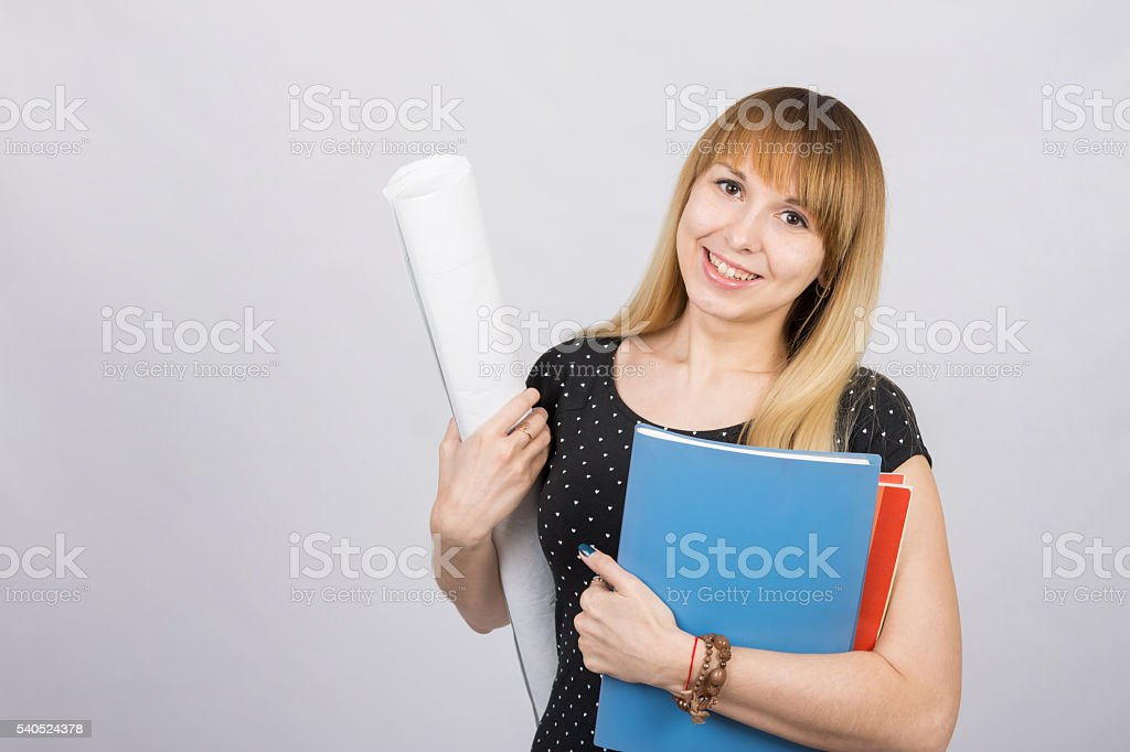 Girl student smiling and holding blueprints stock photo