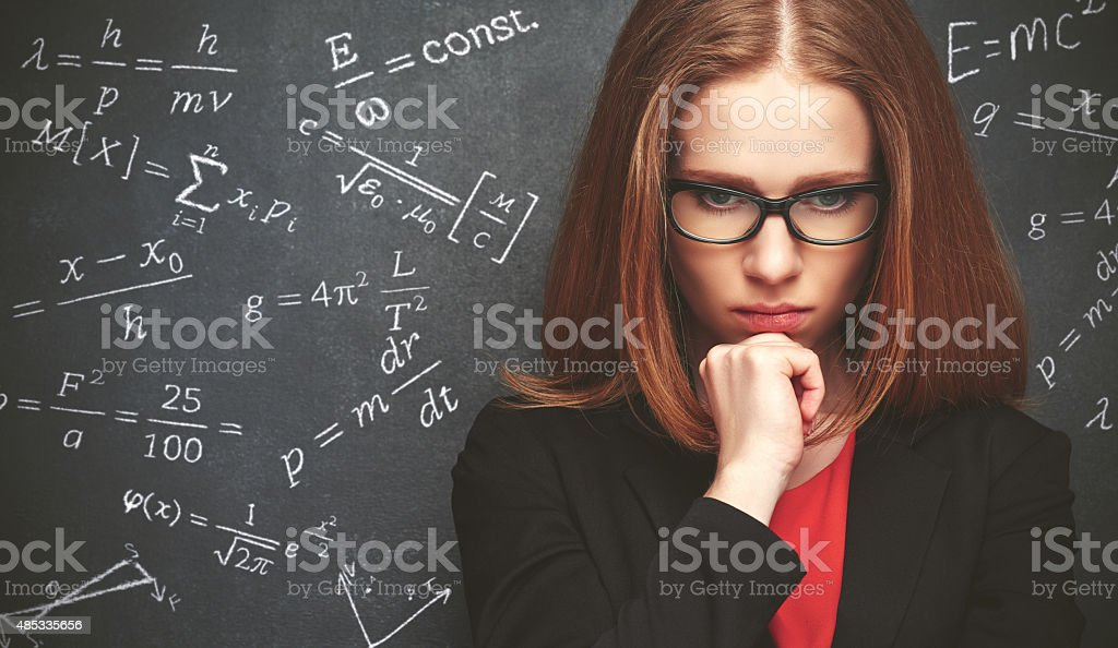 girl student, the teacher writes on  blackboard chalk formula stock photo