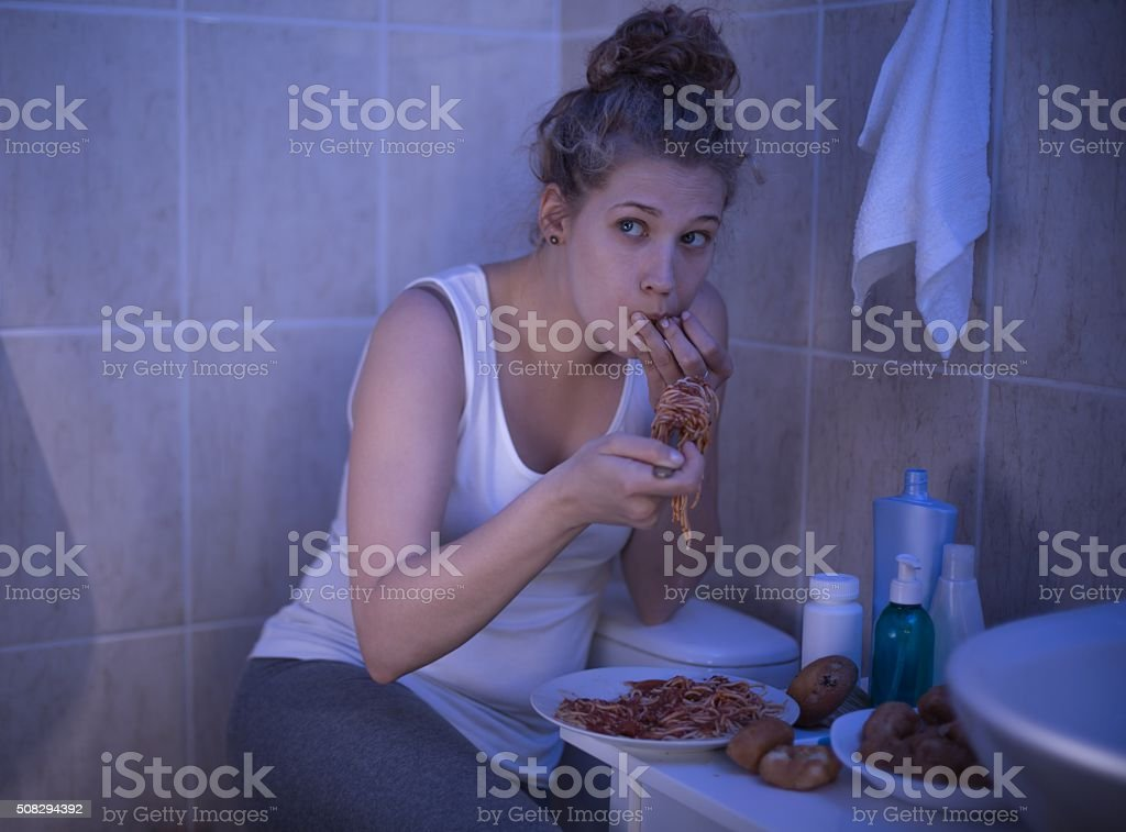 Girl stuffing with spaghetti stock photo