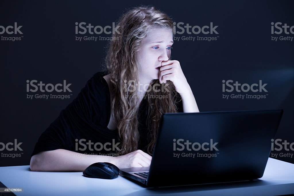 Girl suffering from electronic aggression stock photo