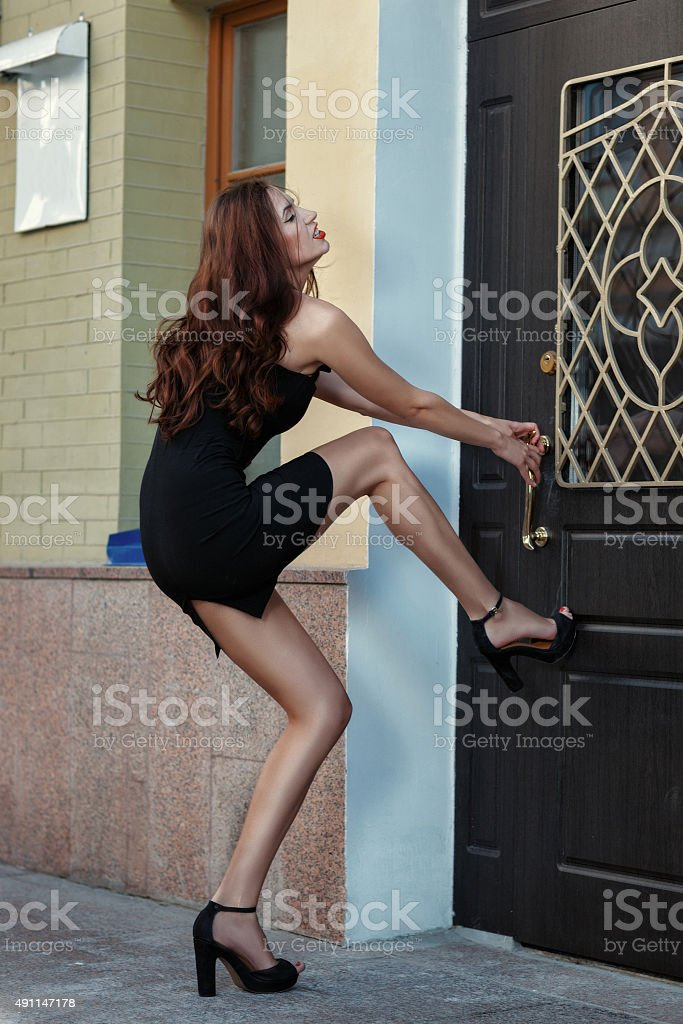 Girl suffers from trying to open the door. stock photo
