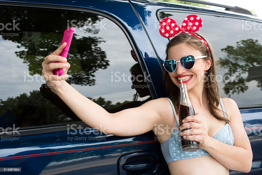 girl summer smart phone selfie outdoors in quirky wardrobe stock photo