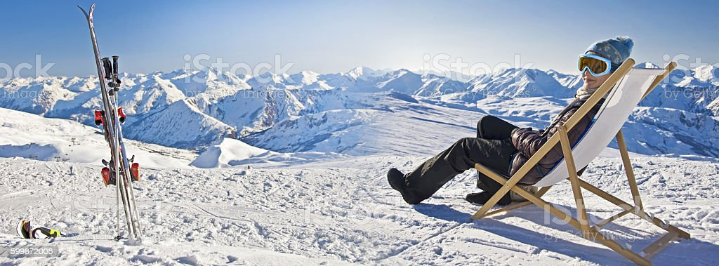 Girl sunbathing in a deckchair near a snowy ski slope stock photo