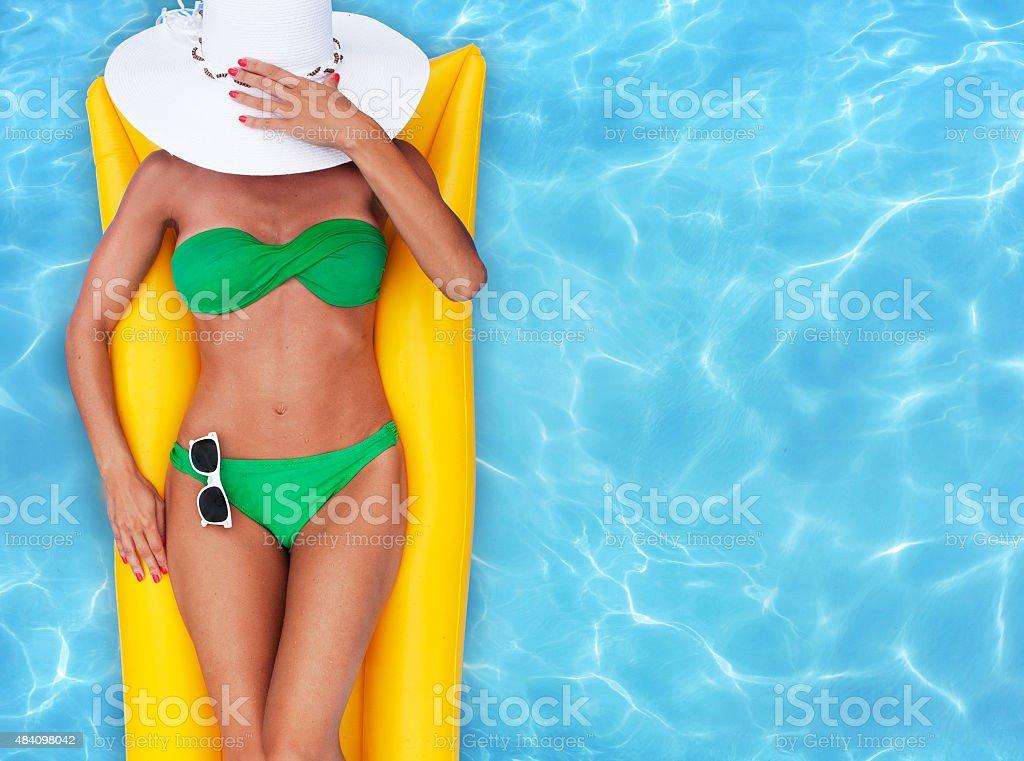 Girl sunbathing in a pool stock photo