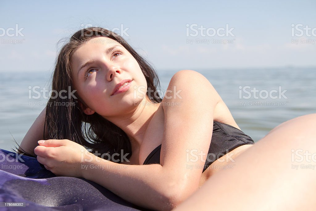 Girl sunbathing on air mattress in sea royalty-free stock photo